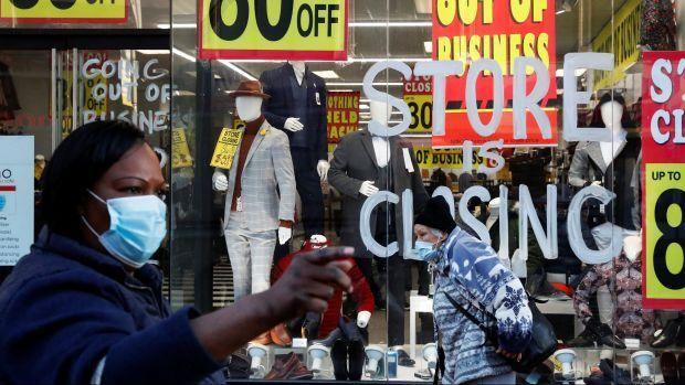 A Black woman walks by a clothing store window advertising a closing sale with several signs saying 80% off.