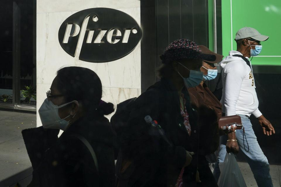 People wearing face masks walk past a Pfizer sign at street level.