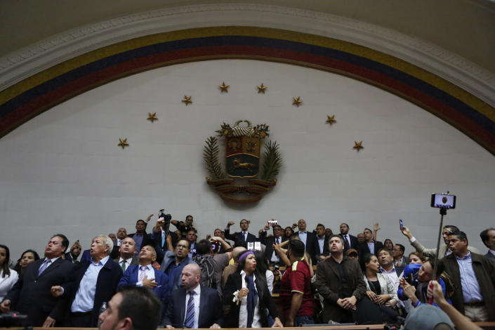 Opposition leader Juan Guaido, top center, and other opposition lawmakers, sing the national anthem after being temporarily blocked form entering the Legislative Palace, as they stand in the main podium area before the start of a session at the National Assembly in Caracas, Venezuela, Tuesday, Jan. 7, 2020. Venezuela's opposition is facing its biggest test yet after government-backed lawmakers announced they were taking control of what Guaidó supporters have described as the nation's last democratic institution. (AP Photo/Andrea Hernandez Briceño)