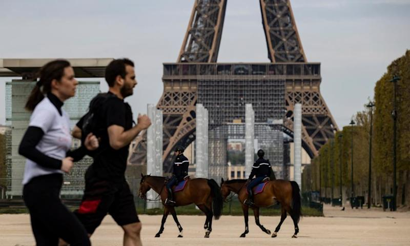 Runners by the Eiffel Tower. Paris has now banned outdoor exercise for much of the day.