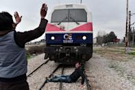 Syrian and Iraqi refugees trapped at the Greek-Macedonian border stop an arriving train during a demonstration in Idomeni, on February 28, 2016 (AFP Photo/Louisa Gouliamaki)