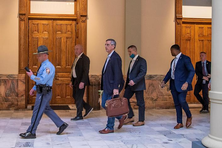 """Lead by a Georgia State Trooper, Georgia Secretary of State Brad Raffensperger, center, exits the Georgia State Capitol building after hearing reports of threats, in Atlanta, Jan. 6, 2021.<span class=""""copyright"""">Alyssa Pointer—Atlanta Journal-Constitution/AP</span>"""