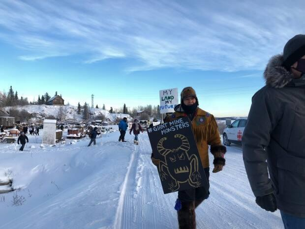 Bobby Drygeese, chairperson of the board of directors for Det'on Cho, the economic development arm of Yellowknives Dene First Nation, walks with a sign at a demonstration in Yellowknife in December of 2020.