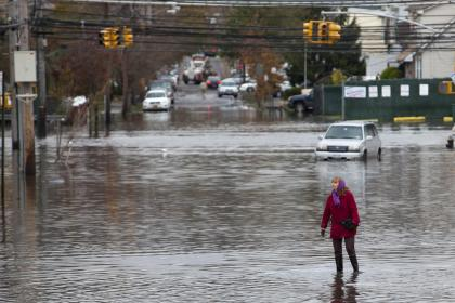 A woman walks through a flooded street in Staten Island. (Reuters)