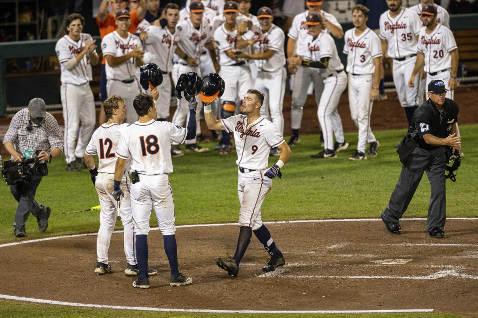 Virginia Chris Newell (9) celebrates his homer in the fifth inning with Logan Michaels (12) and Zack Gelof (18) against Texas during a baseball game in the College World Series Thursday, June 24, 2021, at TD Ameritrade Park in Omaha, Neb. (AP Photo/John Peterson)