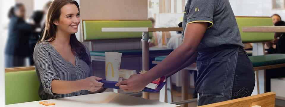 McDonald's employee bringing an order to a woman at a table