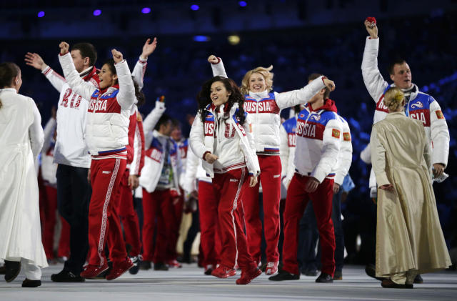 Russian athletes wave to spectators as they arrive during the closing ceremony of the 2014 Winter Olympics, Sunday, Feb. 23, 2014, in Sochi, Russia. (AP Photo/Matt Dunham)