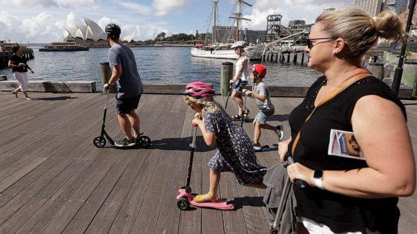 PHOTO: A family rides scooters as they travel along a popular boardwalk overlooking the Opera House in Sydney, Australia, on April 6, 2021. (Rick Rycroft/AP)