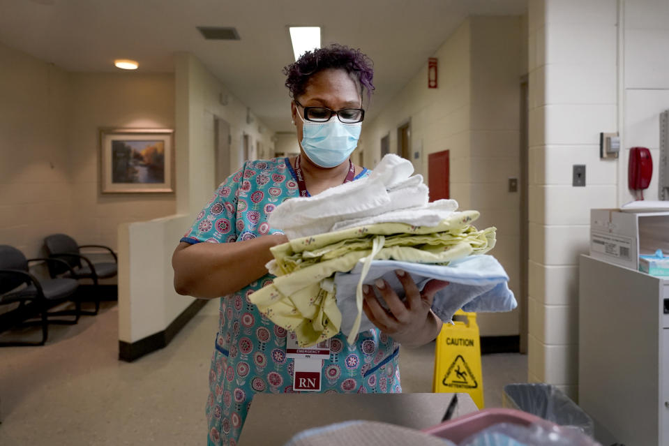 Roseland Community Hospital RN Rhonda Jones, prepares bed linens, towels and a hospital gown Friday, Jan. 29, 2021, for a new patient at the South Side of Chicago hospital. Jones has treated many patients with severe COVID-19, a relative died from it, and her mother and a nephew were infected and recovered, but she is still holding out getting the vaccine. (AP Photo/Charles Rex Arbogast)