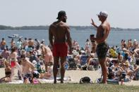 FILE - In this June 5, 2021, file photo, two men talk as crowds gather on L Street Beach in the South Boston neighborhood of Boston. COVID-19 deaths in the U.S. have dipped below 300 a day for the first time since the early days of the disaster in March 2020, while the number of Americans fully vaccinated has reached about 150 million. (AP Photo/Michael Dwyer, File)