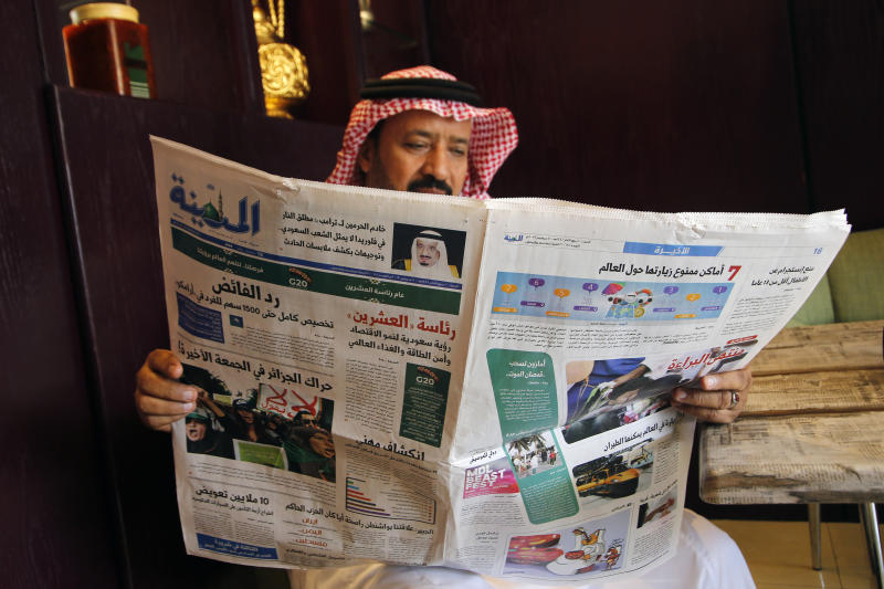 """A man reads the daily Al-Madina newspaper fronted by a picture of Saudi King Salman at a coffee shop in Jiddah, Saudi Arabia, Saturday, Dec. 7, 2019. U.S. law enforcement officials were digging into the background of the suspected Florida naval station shooter Friday, to determine the Saudi Air Force officer's motive and whether it was connected to terrorism. Arabic at top reads """"King Salman to Donald J. Trump: the Florida shooter does not represent the Saudi people."""" (AP Photo/Amr Nabil)"""