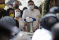 A Philippine flag is placed on top of the urn of former Philippine President Benigno Aquino III during state burial rites on Saturday, June 26, 2021 at a memorial park in suburban Paranaque city, Philippines. Aquino was buried in austere state rites during the pandemic Saturday with many remembering him for standing up to China over territorial disputes, striking a peace deal with Muslim guerrillas and defending democracy in a Southeast Asian nation where his parents helped topple a dictator. He was 61. (AP Photo/Aaron Favila)