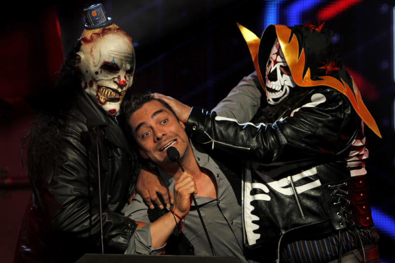 "FILE - In this Oct. 6, 2011 file photo, Mexican comedian and host of the MTV Game Awards Omar Chaparro, center, gestures as he is held by professional wrestlers 'La Parka' and 'Diabolic Clown' during the awards ceremony in Mexico City. Chaparro presented his music album ""Gori Gori"" on Tuesday, July 31, 2012 at a press conference in Mexico City. ( AP Photo/Marco Ugarte, File)"