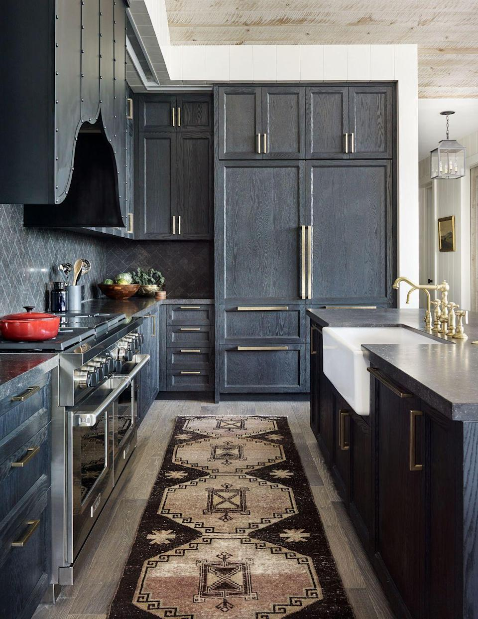 "<p>In this Montana kitchen designed by <a href=""http://palmerweiss.com/"" rel=""nofollow noopener"" target=""_blank"" data-ylk=""slk:Palmer Weiss"" class=""link rapid-noclick-resp"">Palmer Weiss</a>, cabinetry finished in a rich black with blue undertones (<a href=""http://www.provincialstorefixtures.com/"" rel=""nofollow noopener"" target=""_blank"" data-ylk=""slk:Provincial Store Fixtures"" class=""link rapid-noclick-resp"">Provincial Store Fixtures</a>) and a custom bronze hood designed with straps and rivets lends a Western sensibility. Silicon bronze brushed pulls, <a href=""https://www.rockymountainhardware.com/"" rel=""nofollow noopener"" target=""_blank"" data-ylk=""slk:Rocky Mountain Hardware"" class=""link rapid-noclick-resp"">Rocky Mountain Hardware</a>. Dual fuel range, <a href=""https://www.subzero-wolf.com/wolf/ranges"" rel=""nofollow noopener"" target=""_blank"" data-ylk=""slk:Wolf"" class=""link rapid-noclick-resp"">Wolf</a>.</p><p><a class=""link rapid-noclick-resp"" href=""https://go.redirectingat.com?id=74968X1596630&url=https%3A%2F%2Fwww.farrow-ball.com%2Fen-us%2Fpaint-colours%2Frailings&sref=https%3A%2F%2Fwww.veranda.com%2Fdecorating-ideas%2Fcolor-ideas%2Fg28700927%2Fkitchen-paint-colors%2F"" rel=""nofollow noopener"" target=""_blank"" data-ylk=""slk:Get the Look"">Get the Look</a></p>"
