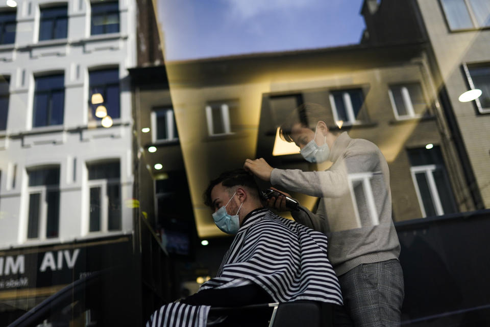 FILE - In this Tuesday, Feb. 16, 2021 file photo, a client, wearing a face mask to prevent against the spread of coronavirus, gets his hair styled at a hairdresser's shop in Brussels. The government on Monday, Feb. 22, 2021 presented scientific projections of the spread of the COVID-19 pandemic in Belgium, indicating it would be very risky to extensively loosen the current restrictions over the coming weeks. (AP Photo/Francisco Seco, File)