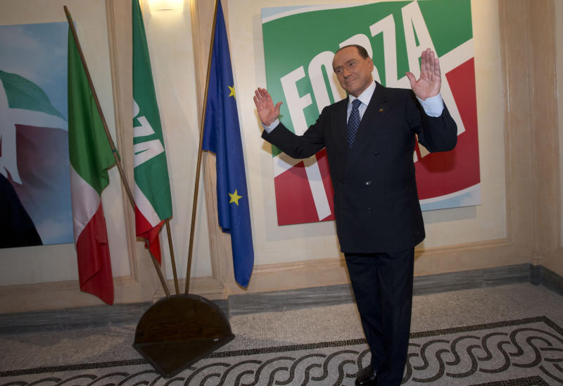 """FILE - In this Thursday, Sept. 19, 2013 file photo, former Italian Premier Silvio Berlusconi pauses for photographers on the occasion of the inauguration the new headquarters of his """"Forza Italia"""" (Go Italy) party, in Rome. Government ministers in former Premier Silvio Berlusconi's political party have announced Saturday, Sept. 28, 2013 their intention to resign their posts, a move that raises tension in the uneasy coalition government and increases the possibility of early elections. Vice Premier Angelino Alfano's spokeswoman said Saturday the five ministers from Berlusconi's center-right People of Freedom Party have decided to submit their resignations. (AP Photo/Andrew Medichini, Files)"""