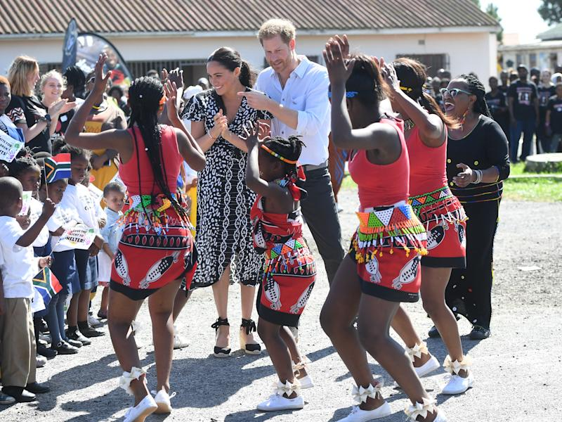 The Duke of Sussex and Duchess of Sussex smile as they dance with locals in Cape Town.
