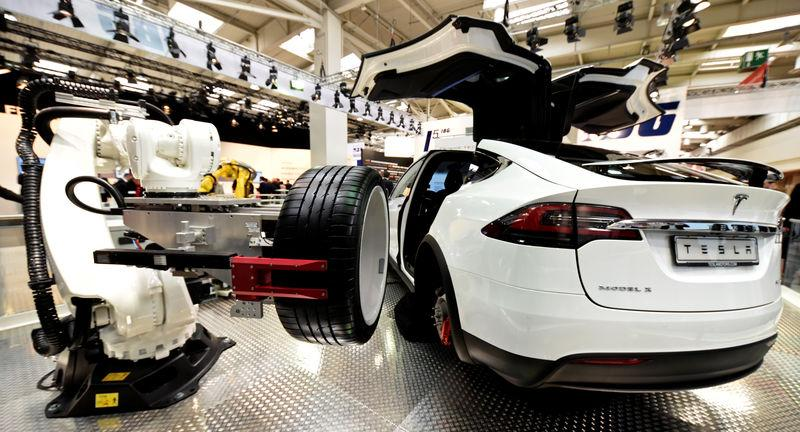 "A robotic arm changes the tyre of a Tesla car at the world's biggest industrial fair, ""Hannover Fair\"