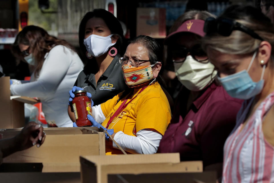 Volunteers prepare donations for delivery to those affected by COVID-19 on tribal lands Thursday, June 25, 2020, in Tempe, Ariz. The resource drive is for families isolated due to COVID-19 on Navajo, Hualapai, Havasupai and White Mountain Apache tribal lands. (AP Photo/Matt York)