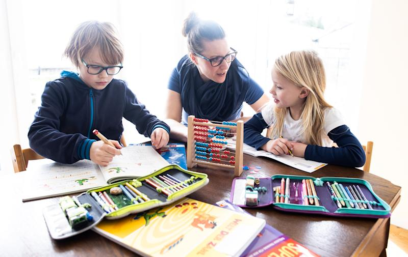 A mother helps her nine-year-old son and six-year-old daughter to do school homework on March 15, 2020 in Dinslaken, Germany. As the number of confirmed cases of coronavirus infection continues to rise daily across Germany so is the impact of the virus on everyday life. Businesses are increasing home office work, airlines are decreasing their flight capacity, schools with cases of the virus are closing temporarily, some sports events are void of spectators, shops are selling out of disinfectants and large-scale public events are being cancelled. (Photo by Lars Baron/Getty Images)