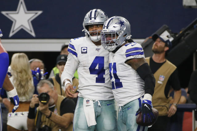 Dallas Cowboys quarterback Dak Prescott (4) celebrates running back Ezekiel Elliott (21) after the connected for a touchdown against the Washington Redskins during the first half of an NFL football game in Arlington, Texas, Sunday, Dec. 15, 2019. (AP Photo/Michael Ainsworth)