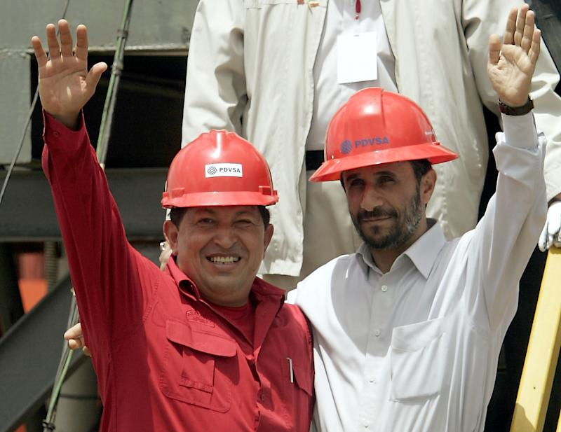 FILE - In this Sept. 18, 2006 file photo, Venezuela's President Hugo Chavez, left, and Iran's President Mahmoud Ahmadinejad wave to the press after inaugurating an oil drill in San Tome, Venezuela. Following Tuesday's death of Hugo Chavez, Venezuela faces near-term political uncertainty that could bring further turmoil to its oil industry.  The country's oil exports fell by nearly half during Chavez's 14 years as president and that kind of decline is not easily reversed. It will take years of investment to turn around the country's beleaguered oil sector.  (AP Photo/Fernando Llano, File)