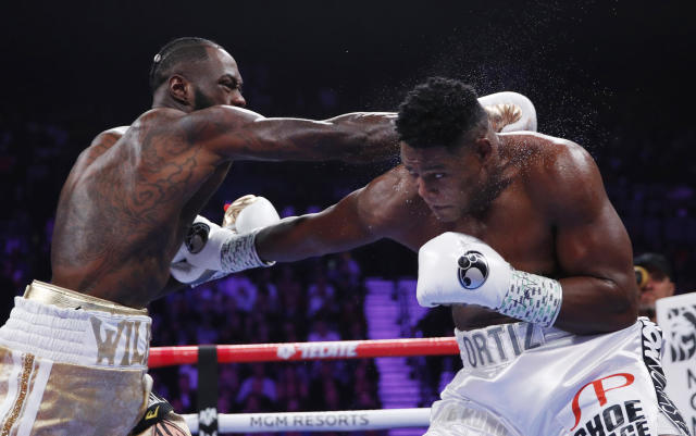 Deontay Wilder, left, and Luis Ortiz trade punches during a heavyweight title boxing match Saturday, Nov. 23, 2019, in Las Vegas. (AP Photo/John Locher)