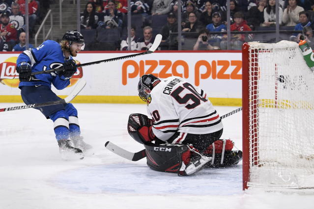Winnipeg Jets' Kyle Connor (81) scores a short-handed goal on Chicago Blackhawks goaltender Corey Crawford (50) during second period NHL hockey action in Winnipeg, Manitoba on Sunday, Feb. 9, 2020. (Fred Greenslade/The Canadian Press via AP)