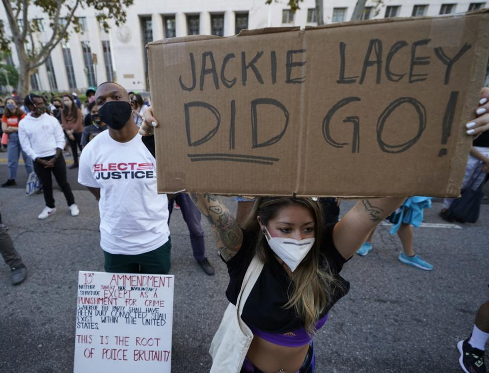 Protesters gather outside the gated Hall of Justice to protest Los Angeles District Attorney Jackie Lacey in downtown Los Angeles Wednesday, Nov. 4, 2020. Former San Francisco District Attorney George Gascon led two-term incumbent Lacey with 54% of more than 2.7 million votes counted by Wednesday. (AP Photo/Damian Dovarganes)