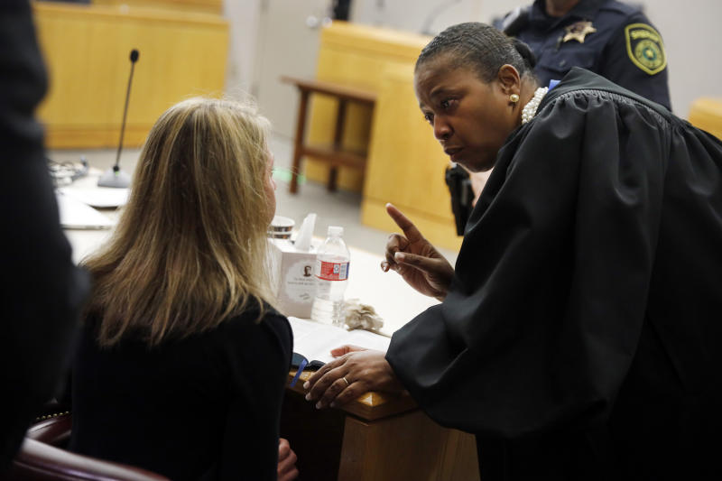 Former Dallas Police Officer Amber Guyger, left, listens to words of advice and encouragement from State District Judge Tammy Kemp after the judge had given her a Bible and before Guyger left for jail, Wednesday, Oct. 2, 2019, in Dallas. Guyger, who said she mistook neighbor Botham Jean's apartment for her own and fatally shot him in his living room, was sentenced to a decade in prison. (Tom Fox/The Dallas Morning News via AP, Pool)