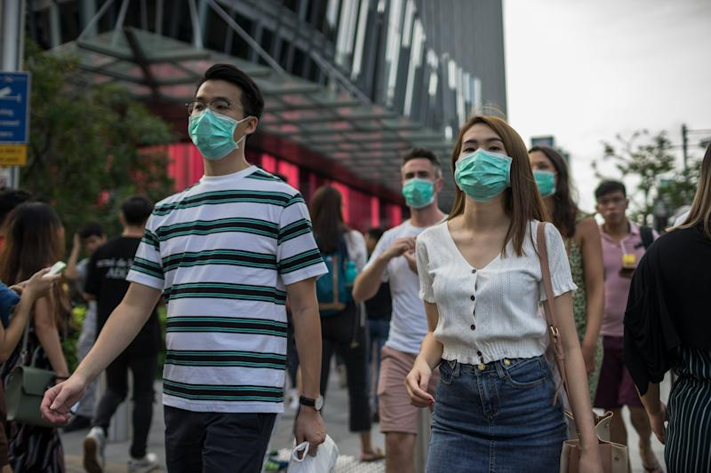 SINGAPORE - 2020/02/14: People wearing protective face masks walks along Orchard Road, a famous shopping district in Singapore, on Valentine's Day. Singapore declared the COVID-19 outbreak as Code Orange on February 7, 2020. (Photo by Maverick Asio/SOPA Images/LightRocket via Getty Images)