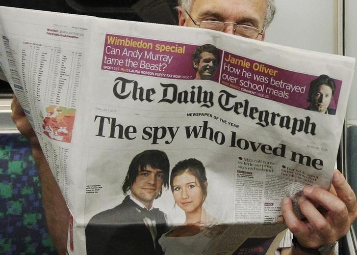 Passenger reads the Daily Telegraph newspaper, featuring a front page interview with the ex-husband of accused Russian spy Anna Chapman, on the underground in London