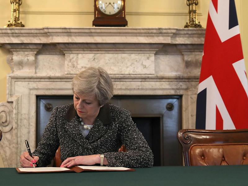 Theresa May signing the document in the Cabinet room (PA)