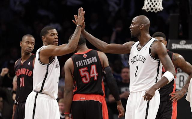 Brooklyn Nets' Kevin Garnett, right, and Joe Johnson celebrate during the first half of Game 3 of an NBA basketball first-round playoff series against the Toronto Raptors on Friday, April 25, 2014, in New York. (AP Photo/Frank Franklin II)