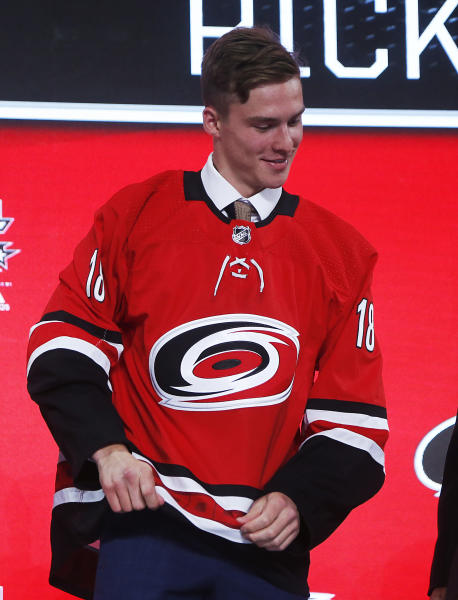 Andrei Svechnikov, of Russia, wears a jersey after being selected by the Carolina Hurricanes during the NHL hockey draft in Dallas, Friday, June 22, 2018. (AP Photo/Michael Ainsworth)