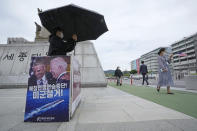 """A protester stands in protest to denounce the U.S. policies on North Korea near the U.S. Embassy in Seoul, South Korea, Tuesday, Sept. 28, 2021. North Korea on Monday accused the United States of keeping up its """"hostile policy"""" and demanded the Biden administration permanently end joint military exercises with South Korea even as it continued its recent streak of weapons tests apparently aimed at pressuring Washington and Seoul over slow nuclear diplomacy. The sign reads """"Suspension of war practice against North Korea and withdrawal of the U.S. troops."""" (AP Photo/Ahn Young-joon)"""