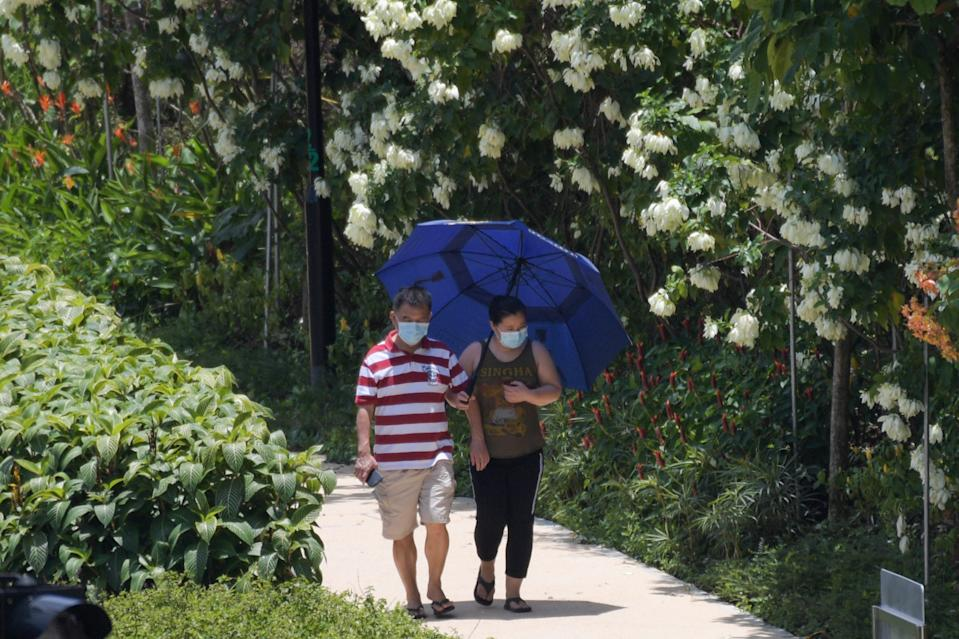 A couple wearing face masks in Singapore on 22 March, 2020. (PHOTO: AFP via Getty Images)