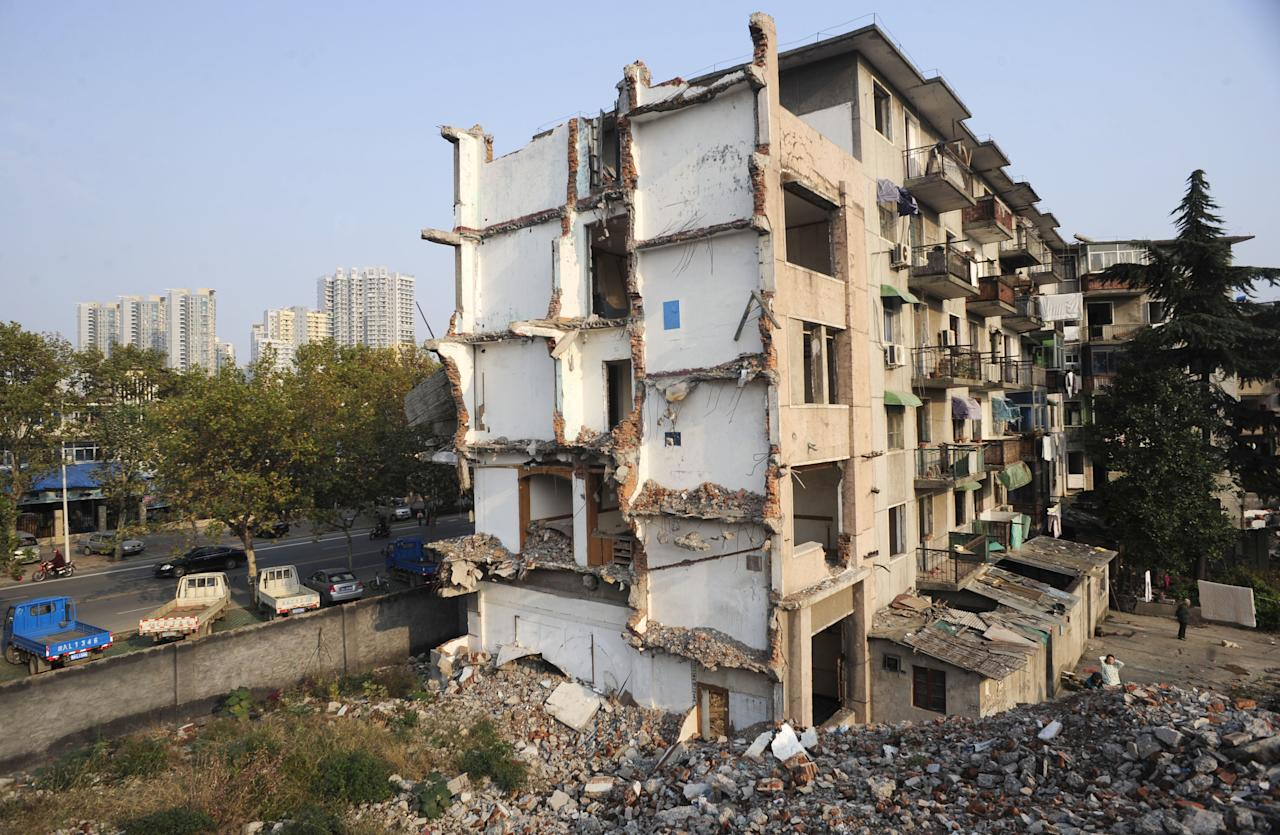17 families are refusing to move out even though contractors have begun to demolish the building (Rex Features)