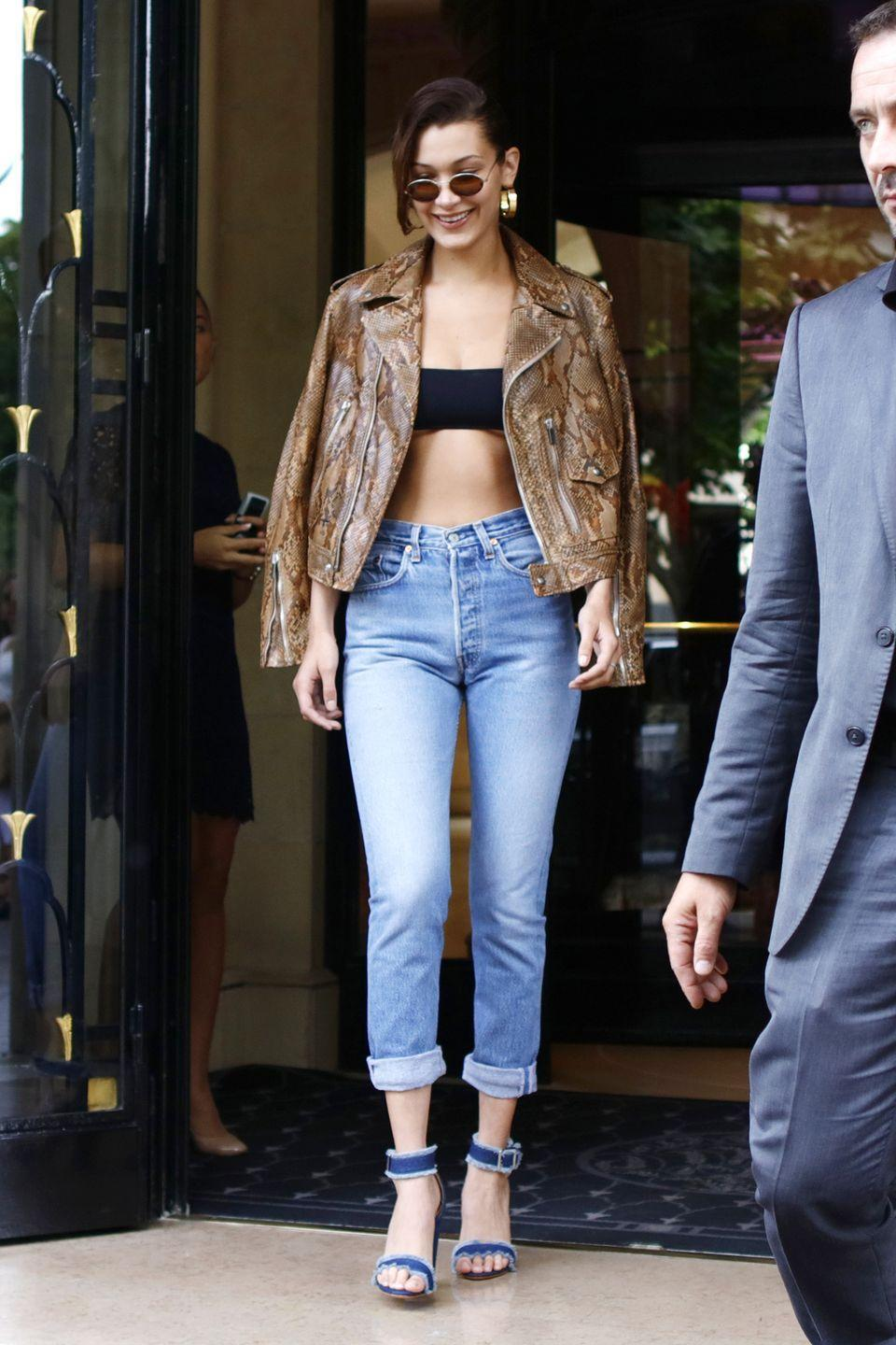 <p>In a snakeskin jacket, Dior black bandeau top, high-waisted jeans, Schutz denim sandals and Robert & Fraud sunglasses while out in Paris. </p>