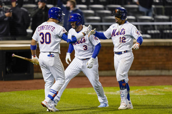 New York Mets' Francisco Lindor (12) celebrates with Tomas Nido (3) and Michael Conforto (30) after hitting a two-run home run off Arizona Diamondbacks pitcher Caleb Smith during the seventh inning of a baseball game Friday, May 7, 2021, in New York. (AP Photo/John Minchillo)