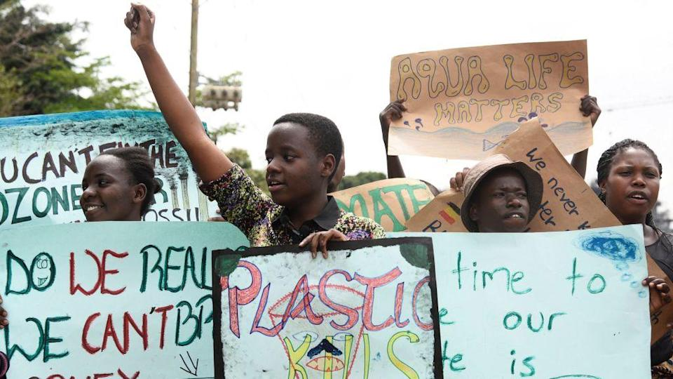 Leah Namugerwa carries a placard and gestures as she leads Ugandan students in taking part in the global 'School Strike for Climate' in Kampala