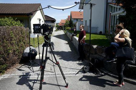 TV crews perpare for a statement in front of a house in Wuerenlingen, Switzerland May 10, 2015. REUTERS/Ruben Sprich