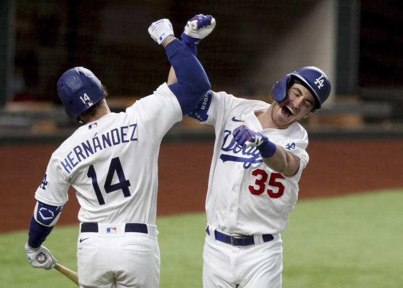 Los Angeles Dodgers' Cody Bellinger, right, smashes his right forearm against Kike Hernandez's right forearm.