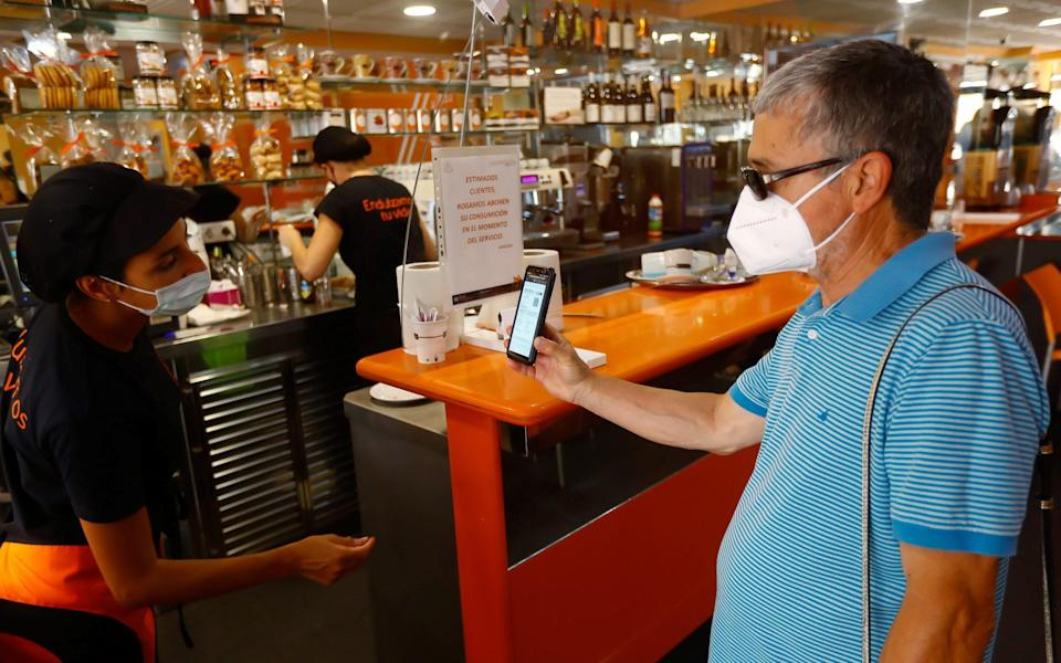 A staff member at a coffee shop reviews a digital vaccination certificate as the Canary Islands government imposed stricter rules to control a surge in Covid-19 cases - REUTERS