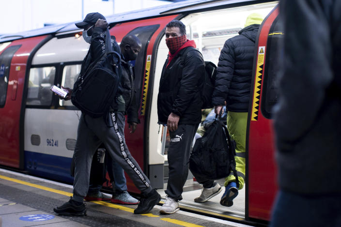 Commuters alight from a tube train wearing face masks at Canning Town station in London after a rail fare increase came into effect on Monday March 1, 2021. Ticket prices have increased Monday, as people are still encouraged to work from home if possible, because of the coronavirus pandemic. (Aaron Chown/PA via AP)