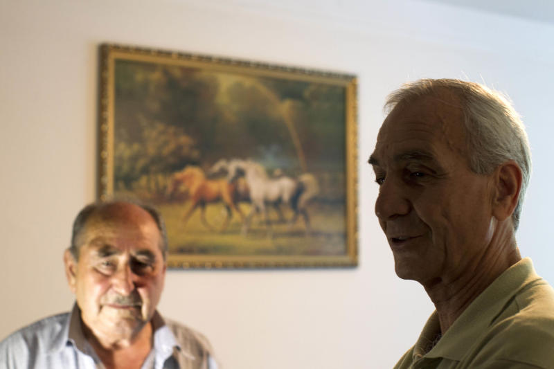 In this Monday, July 23, 2012 photo, ethnic Circassian refugees from Syria Shawkat Achemez Al Sharkas, right, and his neighbor who only identified himself as Faruk, left, sit at a hotel room in Nalchik, Russia. Some 340 ethnic Circassians from Syria came to Russia's Caucasus region this year. Czarist troops and Cossacks expelled hundreds of thousands of Circassians in the 1860s in what some historians call a genocide and an ethnic cleansing. (AP Photo/Misha Japaridze)