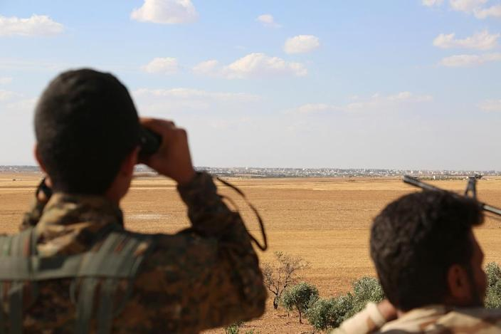 Fighters from the Syrian Democratic Forces (SDF) use binoculars from a view point overlooking the northern Syrian town of Manbij (AFP Photo/Delil Souleiman)