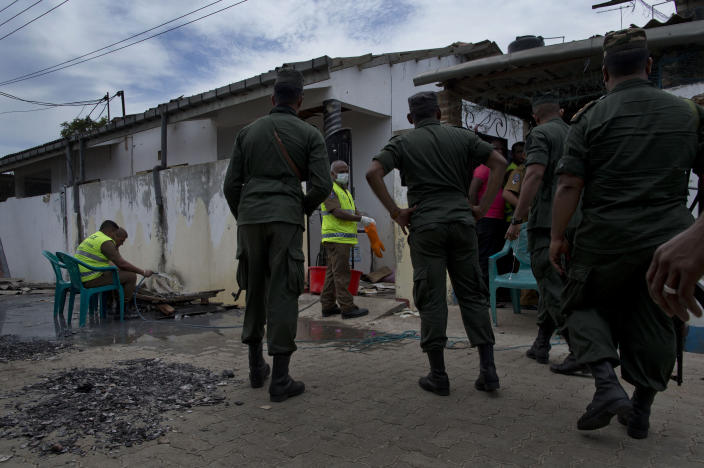 Army officers arrive as police officers collect evidence from a site of a gun battle between troops and suspected Islamist militants in Kalmunai, Sri Lanka, Sunday, April 28, 2019. Police in Ampara showed The Associated Press on Sunday the explosives, chemicals and Islamic State flag they recovered from the site of one security force raid in the region as Sri Lanka's Catholics celebrated at televised Mass in the safety of their homes. (AP Photo/Gemunu Amarasinghe)