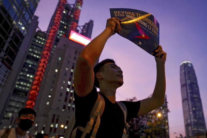 A demonstrator holds a sign opposing the recent firings of Cathay Pacific employees shouts as they gather for a demonstration at the Edinburgh Square in Hong Kong, Wednesday, Aug. 28, 2019. Trade union members in Hong Kong are rallying against the city's flagship Cathay Pacific airline for firing employees linked to ongoing pro-democracy protests. (AP Photo/Vincent Yu)