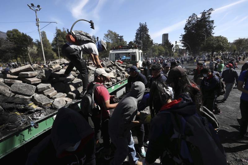 Volunteers dismantle a barricade in a major cleanup effort in the aftermath of violent protests against the government, in Quito, Ecuador, Monday, Oct. 14, 2019. Ecuador celebrated a deal President Lenín Morenoand indigenous leaders struck late Sunday to cancel a disputed austerity package and end nearly two weeks of protests that have paralyzed the economy and left seven dead.(AP Photo/Fernando Vergara)